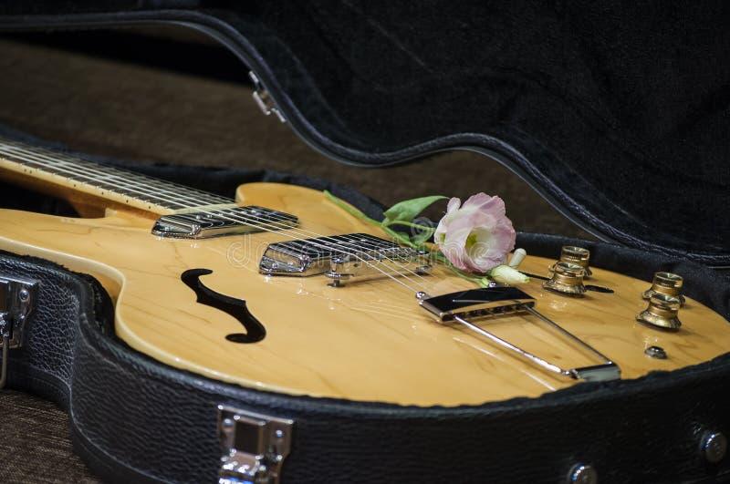 Czarna gitary skrzynka z gitarą elektryczną i kwiatem obrazy royalty free
