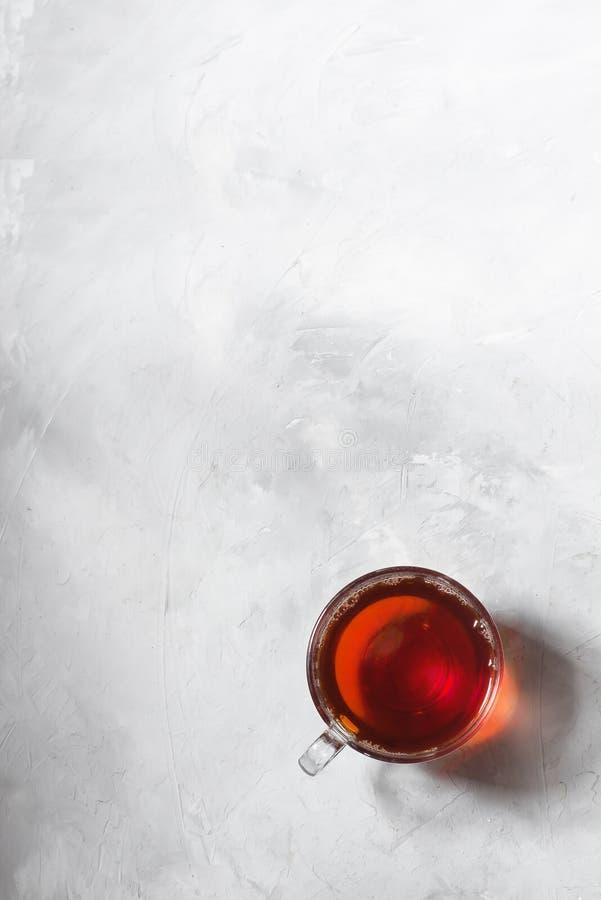 Czarna herbata w szklanym kubku na szarym tle obraz royalty free