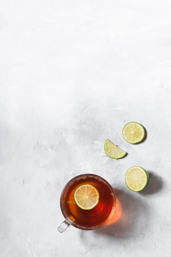 Czarna herbata w szklanym kubku z wapno plasterkami na szarym tle zdjęcia royalty free