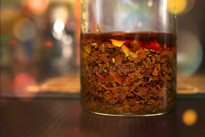 Czarna herbata Warząca w szkle na zmroku Barwionym Drewnianym stole w kuchni w gościu restauracji lub Herbaciana ceremonia Boczny fotografia stock