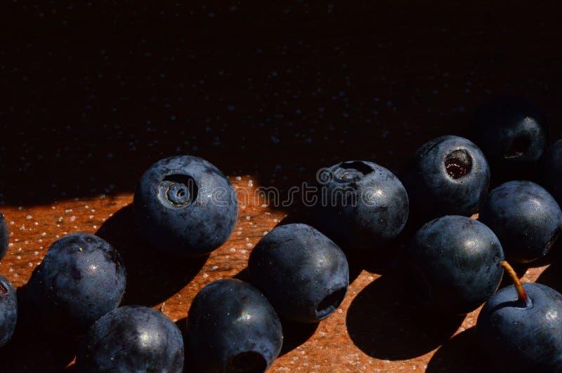 Czarna jagoda jaskrawy dojrzały zmrok - błękit na naturalnym drewnianym tle obraz royalty free
