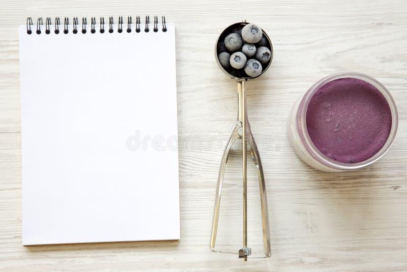 Czarna jagoda lody sorbet w plastikowym słoju, lody miarce z zamarzniętymi czarnymi jagodami i notepad na białym drewnianym tle o obraz stock