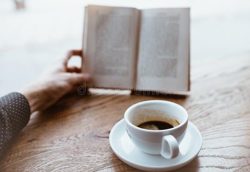 Czarna kawa na spodku z ludzką ręką trzymającą na zamazanym tle książkę na drewnianym stole obok wielkiej kawiarni obrazy stock