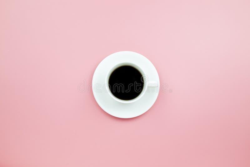 Czarna kawa w białej filiżance na różowych blackground pastelu stylu copys obraz royalty free