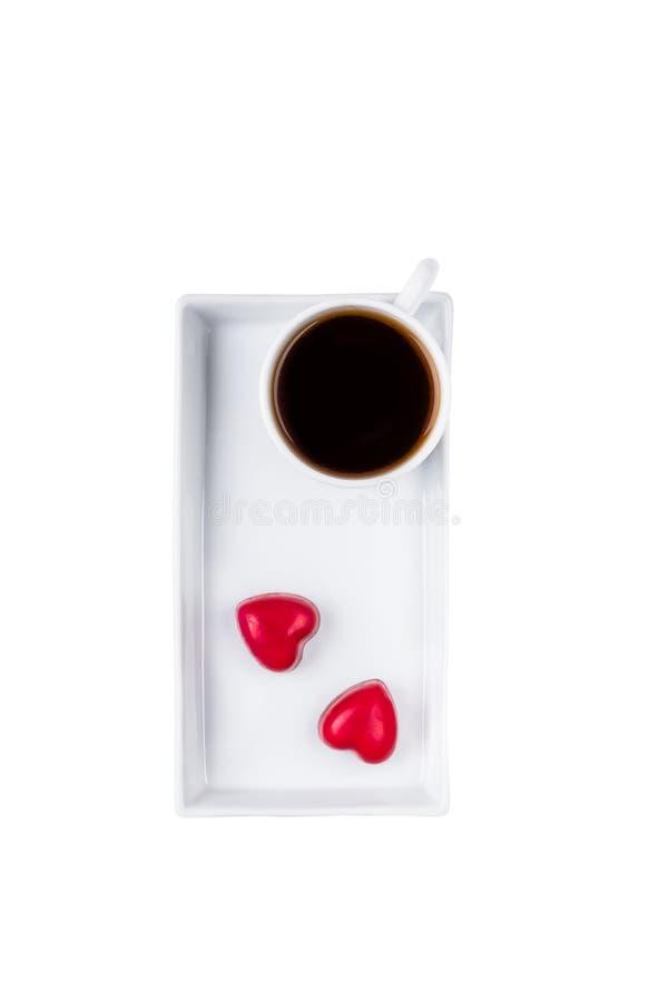 Czarna kawa w białej filiżance odizolowywających na białym tle dwa serc czerwonym cukierku i szczęśliwy dzień valentine s zdjęcie stock