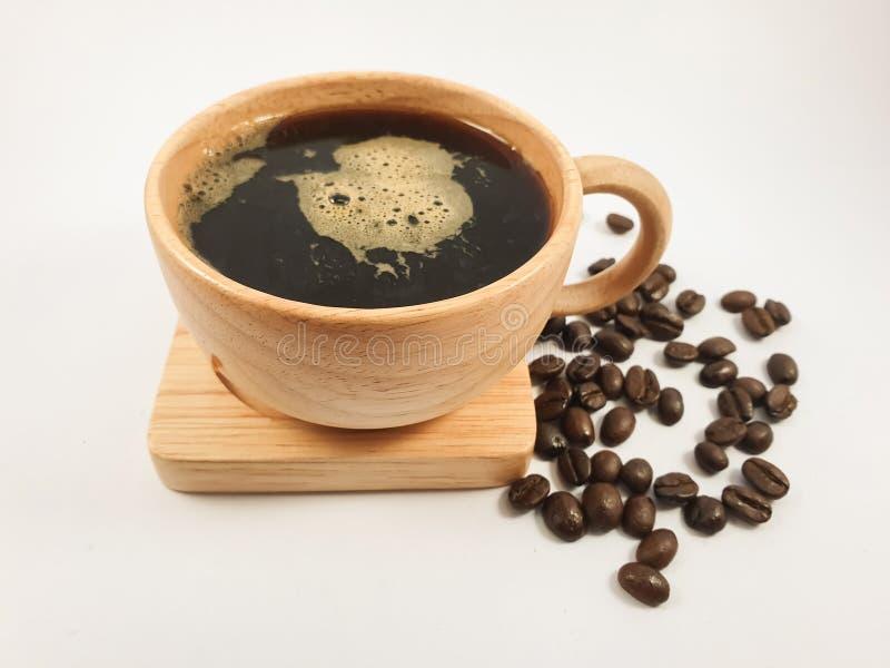 Czarna kawa w drewnianej filiżance, kawowe fasole na starym drewnianym tekstury tle fotografia royalty free