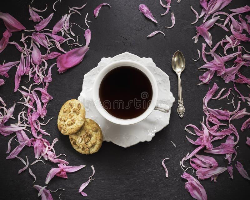 Czarna kawa w filiżance z peonia płatkami zdjęcia stock