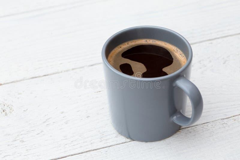 Czarna kawa w niebieskoszarym ceramicznym kubku na bielu malował drewno Przestrze? dla teksta zdjęcia royalty free