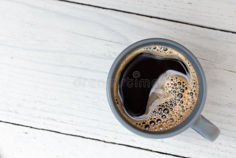 Czarna kawa w niebieskoszarym ceramicznym kubku na bielu malował drewno z góry Przestrze? dla teksta zdjęcie stock