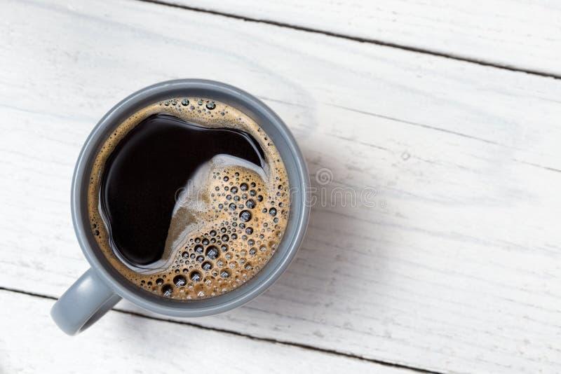 Czarna kawa w niebieskoszarym ceramicznym kubku na bielu malował drewno z góry Przestrze? dla teksta obrazy stock
