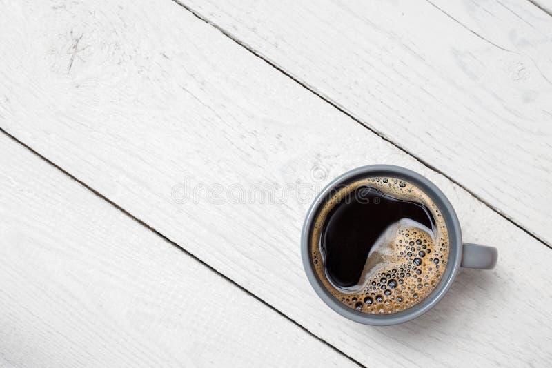 Czarna kawa w niebieskoszarym ceramicznym kubku na bielu malował drewno z góry Przestrze? dla teksta fotografia stock