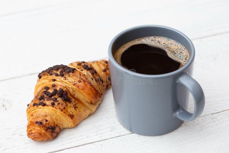 Czarna kawa w niebieskoszarym ceramicznym kubku obok czekoladowego croissant na bielu malował drewno obrazy royalty free