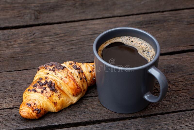 Czarna kawa w niebieskoszarym ceramicznym kubku obok czekoladowego croissant na nieociosanym ciemnego brązu drewna stole zdjęcie stock