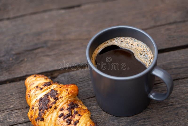 Czarna kawa w niebieskoszarym ceramicznym kubku obok czekoladowego croissant odizolowywającego na nieociosanym ciemnego brązu dre zdjęcia royalty free