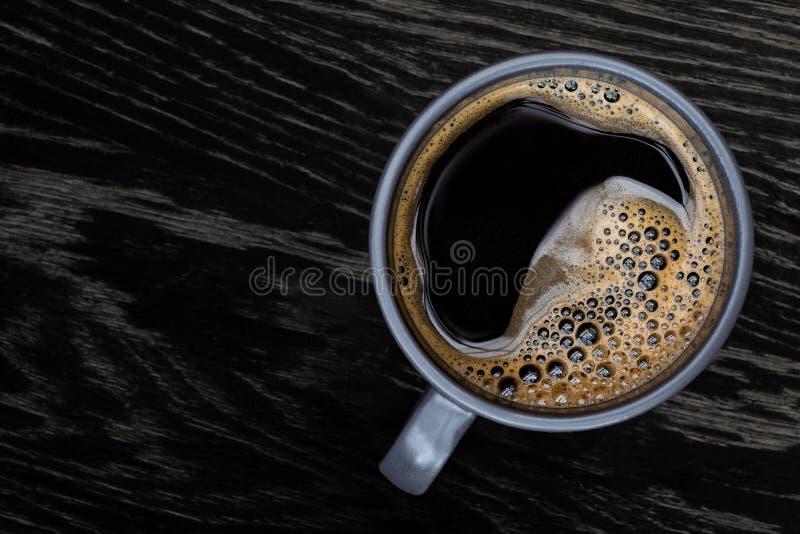 Czarna kawa w niebieskoszarym ceramicznym kubku odizolowywającym na ciemnego brązu drewna stole z adrą z góry Przestrze? dla teks zdjęcia stock