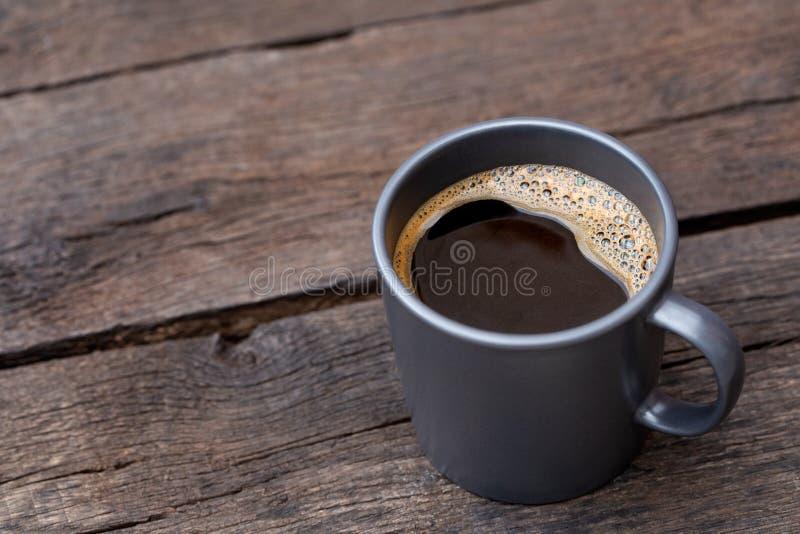 Czarna kawa w niebieskoszarym ceramicznym kubku odizolowywającym na nieociosanym ciemnego brązu drewna stole Przestrze? dla tekst obraz royalty free