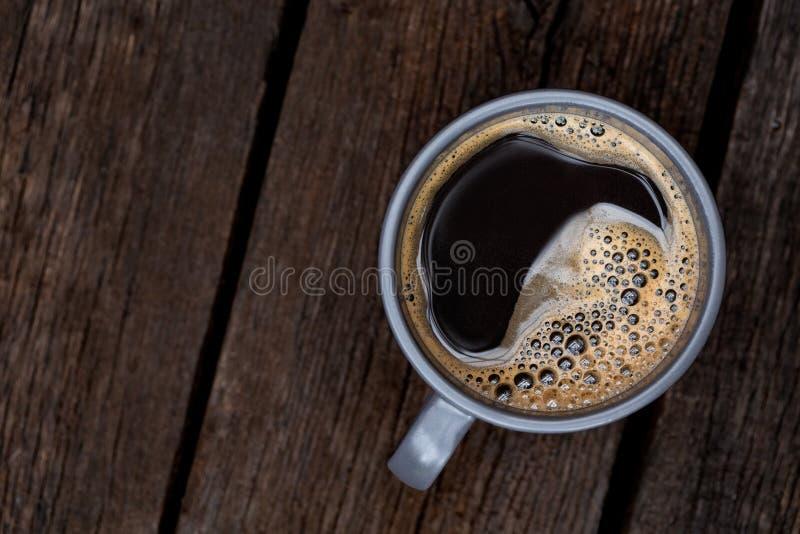 Czarna kawa w niebieskoszarym ceramicznym kubku odizolowywającym na nieociosanym ciemnego brązu drewna stole z góry Przestrze? dl fotografia stock