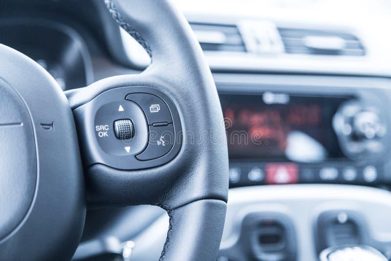 Czarna kierownica z pilotem do tv, nowożytny samochód, rozmyta deska rozdzielcza fotografia royalty free