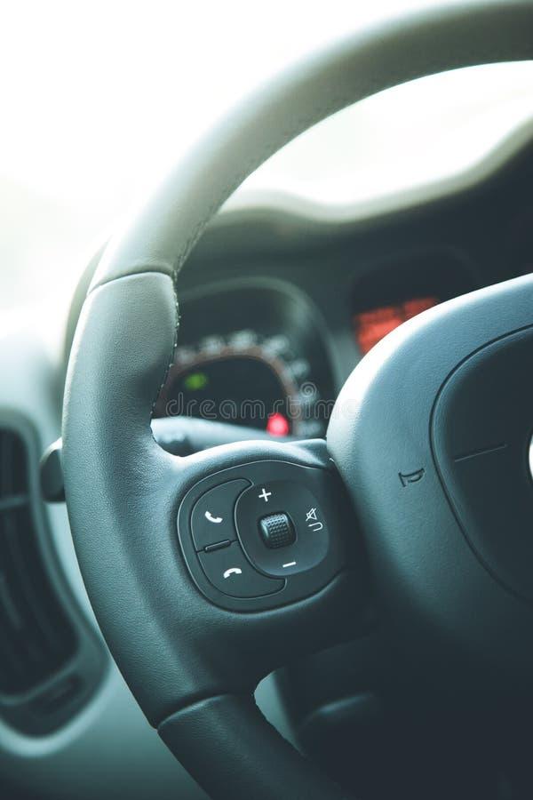Czarna kierownica z pilotem do tv, nowożytny samochód, rozmyta deska rozdzielcza zdjęcie royalty free