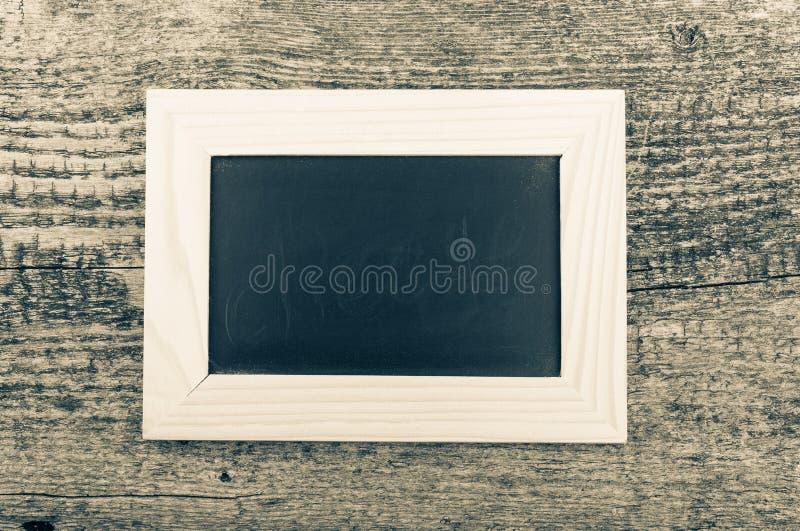 Czarna kredowa deska w lekkiej drewnianej ramie na starym drewnianym tabl zdjęcia royalty free