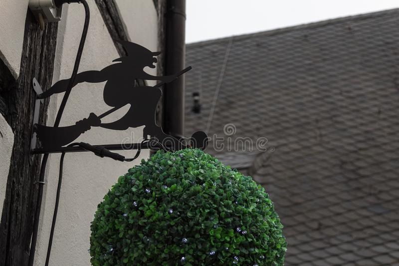 Czarna kruszcowa czarownica na miotła ilustracyjnym logo na budynek stronie Germany fotografia stock