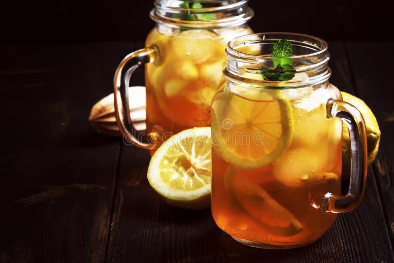 Czarna lodowa herbata z cytryna plasterkiem w szklanym słoju na ciemnym kuchennego stołu tle, lato chłodno miękki napój, selekcyj zdjęcia stock
