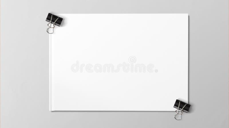 Czarna papierowa klamerka odizolowywająca na białej księdze na popielatym tle fotografia royalty free