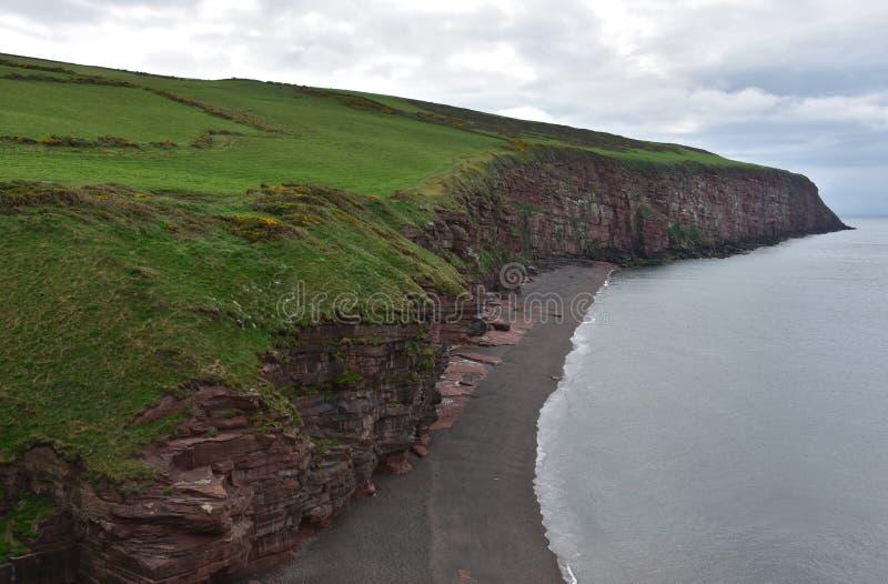 Czarna piasek plaża z rewolucjonistki skały Dennymi falezami w Anglia zdjęcia royalty free