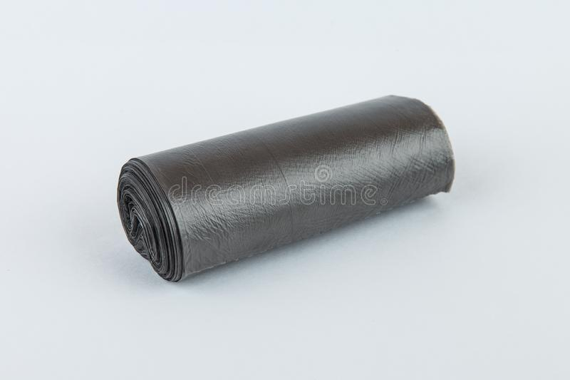 Czarna plastikowa polietylen toreb na śmiecie rolka odizolowywająca nad białym tłem obraz royalty free