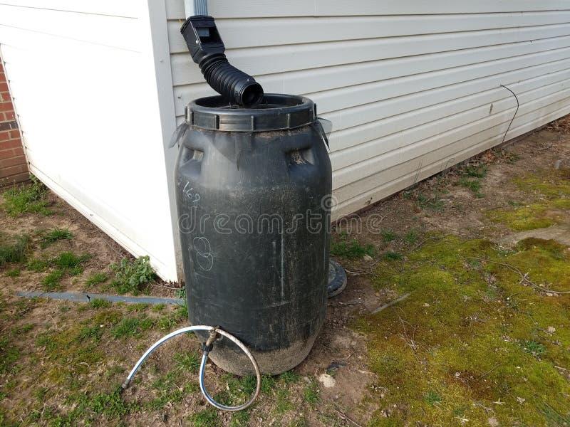 Czarna podeszczowa baryłka z rynnowym downspout i wężem elastycznym zdjęcia stock