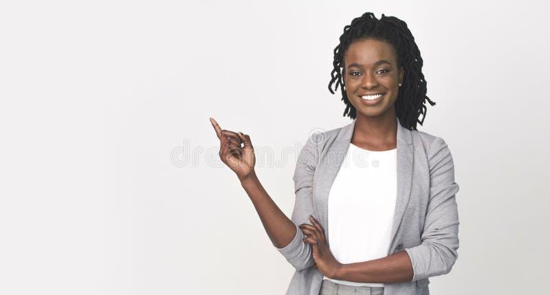 Czarna Służbowa Kobieta Wskazująca Palec Na Pustej Przestrzeni Na Biało obrazy royalty free