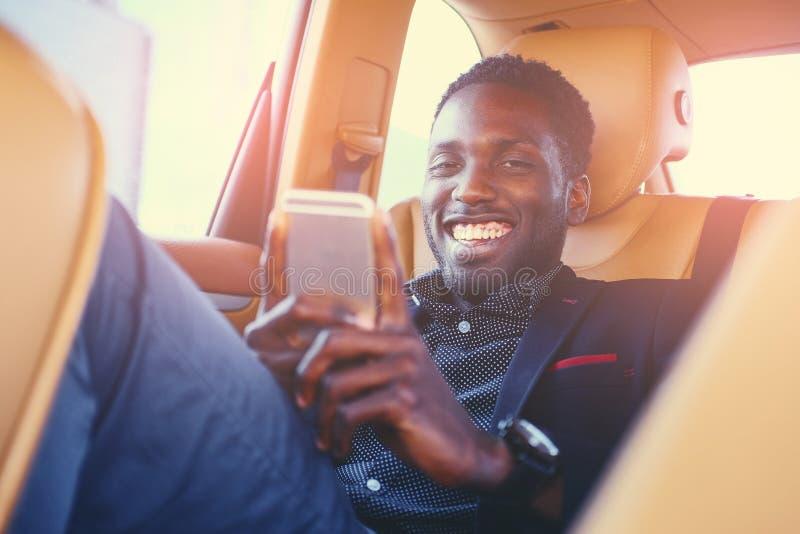 Czarna samiec używa mądrze telefon w samochodzie obraz royalty free