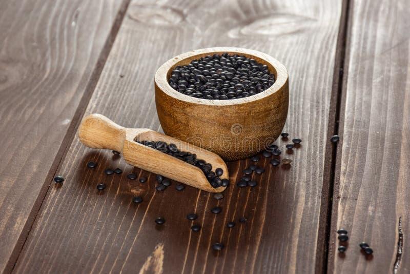 Czarna soczewicy bieługa na brązu drewnie obraz stock