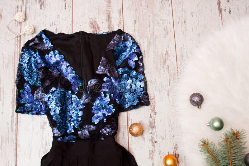 Czarna suknia z błękitnymi cekinami na drewnianym tle, Bożenarodzeniowe piłki na białym futerku modny pojęcie obrazy stock