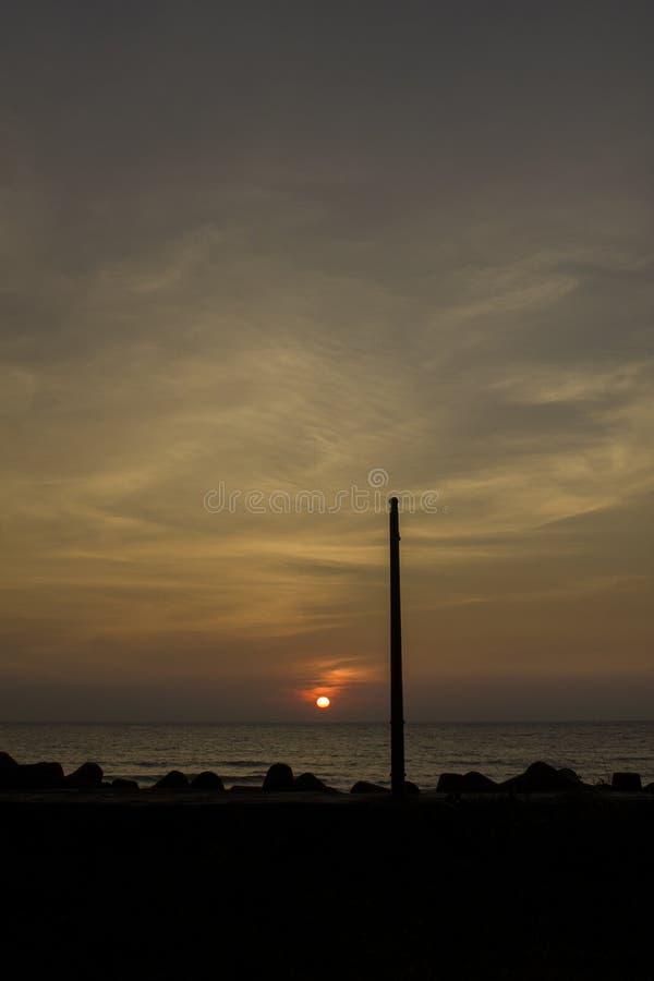 Czarna sylwetka lamppost na dennym deptaku z tetrapods przeciw tłu ocean pod wieczór zmierzchem zdjęcie royalty free