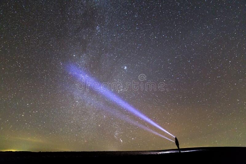Czarna sylwetka mężczyzna z kierowniczą latarki pozycją na zielonym trawiastym polu, długi błękita promień przez pięknego ciemneg zdjęcia royalty free