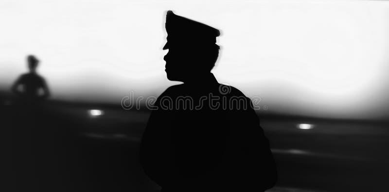 Czarna sylwetka na ściennym tle umundurowany funkcjonariusz policji zdjęcie royalty free