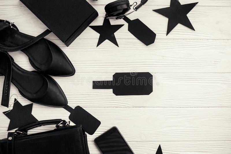 Czarna torba, prezenta pudełko, czarne metki, telefon, buty na białym bac fotografia stock