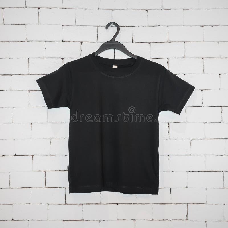 Czarna wisząca koszula na ścianie z cegieł w nowożytnej pojęcie reklamie Pusty bawełna mundur dla twój projekta obraz stock