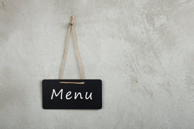 Czarna zawiadomienie deska, blackboard, chalkboard z teksta menu na popielatej cement ścianie fotografia royalty free