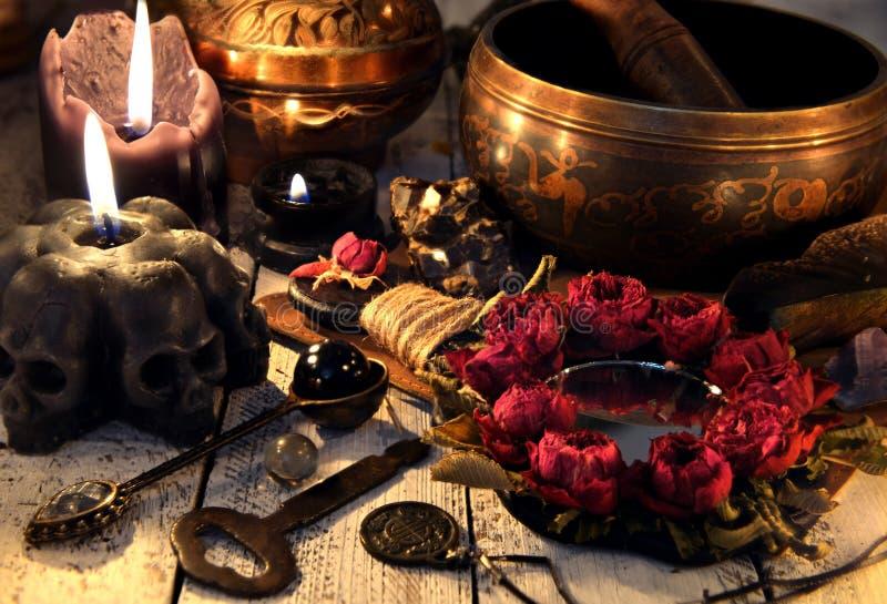 Czarne świeczki z czaszkami, róży lustrem, metalu kluczem i śpiewu pucharem na czarownica stole, obrazy royalty free
