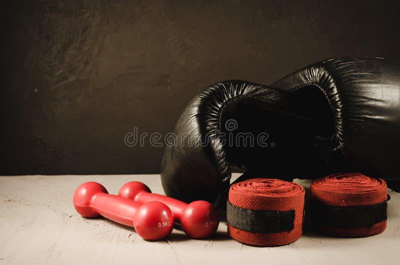 czarne bokserskie rękawiczki, czerwoni dumbbells, bandaż i sporta pojęcie z/czarnymi bokserskimi rękawiczkami, czerwonymi dumbbel fotografia stock