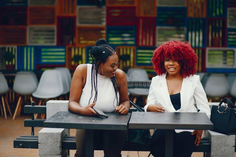 Czarne dziewczyny siedzi w kawiarni obrazy stock