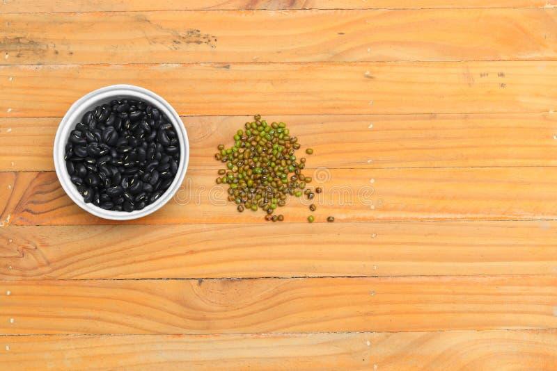 Czarne fasole w pucharze i zieleni zbliżeniu na drewnianym podłogowym tle zdjęcia stock