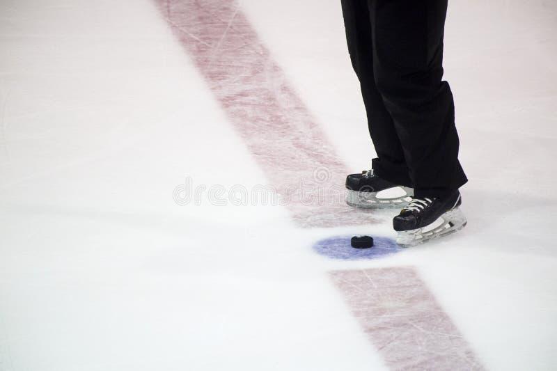 Czarne hokejowego krążka hokojowego i arbitra nogi na lodowym lodowisku sport na śnieg na zimę zdjęcia royalty free