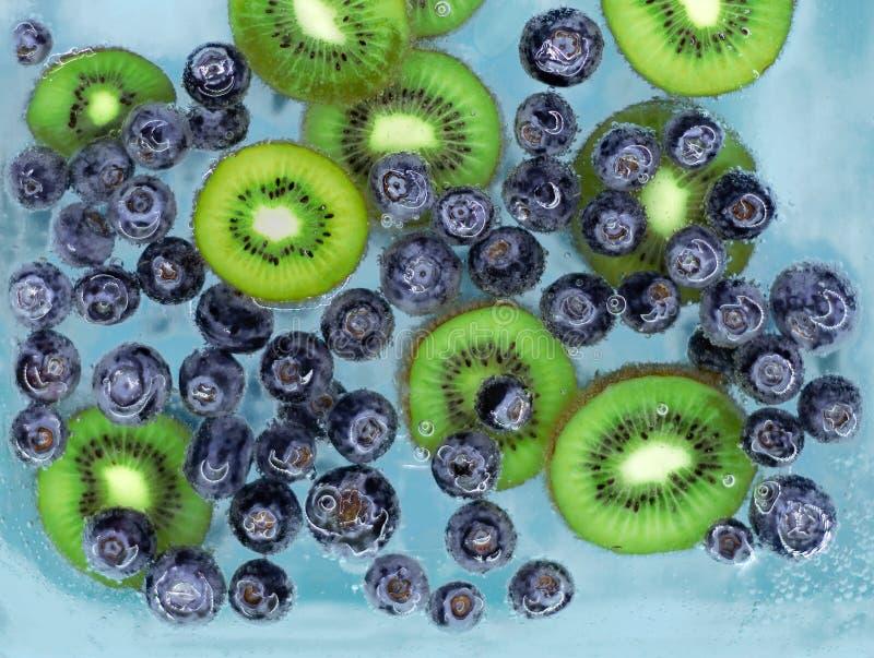 Czarne jagody i kiwi słabnięcie w błękitne wody z lotniczymi bąblami zdjęcie royalty free