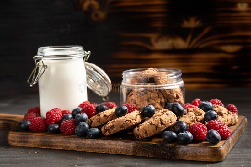 Czarne jagody, malinki i ciastka umieszczający nad drewnianym półmiskiem, fotografia royalty free