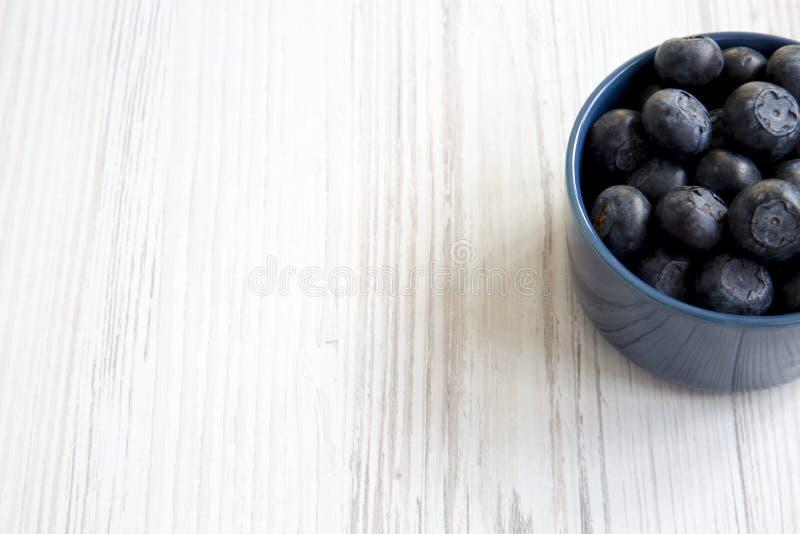 Czarne jagody w błękitnym pucharze, boczny widok Świeża borówka na białym drewnianym tle fotografia stock