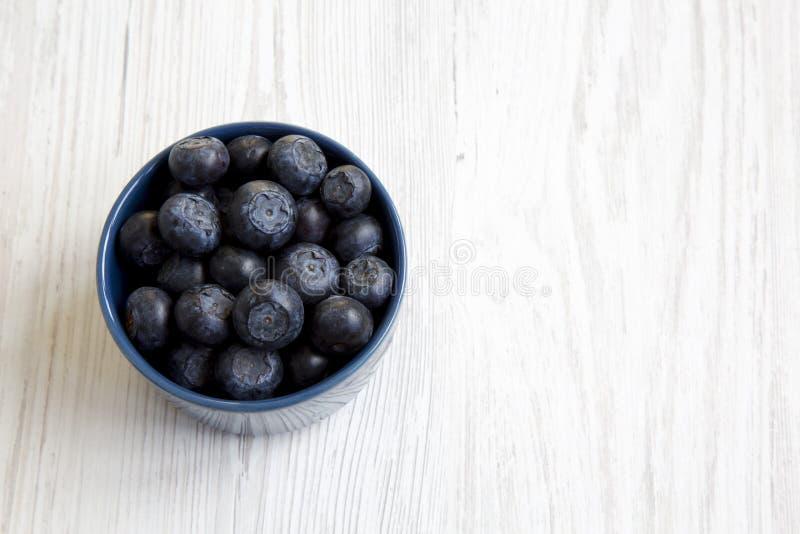 Czarne jagody w błękitnym pucharze, odgórny widok Świeża borówka na białym drewnianym stole obrazy royalty free