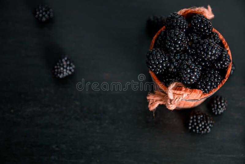 Czarne malinki w drewnianym koszu na tle Rama kosmos kopii Odgórny widok obraz stock